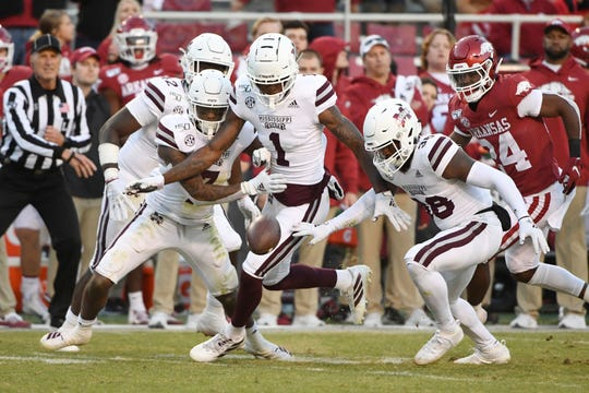 Mississippi State defenders Marcus Murphy (7), Martin Emerson (1) and Fred Peters (38) go after an Arkansas fumble during the second half of an NCAA college football game, Saturday, Nov. 2, 2019, in Fayetteville, Ark.