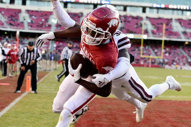 Arkansas receiver Mike Woods pulls in a touchdown catch in front of Mississippi State defender Jay Jimison in the second half of an NCAA college football game, Saturday, Nov. 2, 2019 in Fayetteville, Ark.