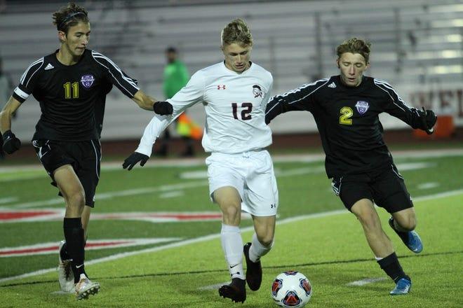 Lexington's Mason Blashak (11) and Isaac Weber (2) put the squeeze on Lima Shawnee's Jacob Miller.
