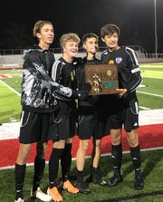 Lexington's four captains show off the regional soccer championship plaque earned with Saturday's 3-2 win over Lima Shawnee.