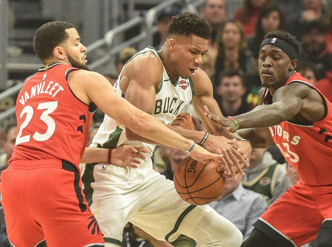 The Raptors' Fred VanVleet (23) and Pascal Siakam   pressure Giannis Antetokounmpo on Saturday night and Fiserv Forum.