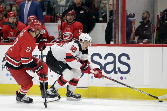 New Jersey Devils center Jack Hughes (86) skates while Carolina Hurricanes defenseman Brett Pesce (22) chases during the first period of an NHL hockey game in Raleigh, N.C., Saturday, Nov. 2, 2019.