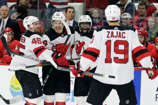 New Jersey Devils defenseman Sami Vatanen (45), left wing Miles Wood (44), defenseman P.K. Subban (76) and center Travis Zajac (19) celebrate Subban's goal against the Carolina Hurricanes during the third period of an NHL hockey game in Raleigh, N.C., Saturday, Nov. 2, 2019. New Jersey won 5-3.