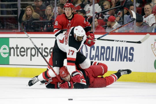 Carolina Hurricanes center Martin Necas (88), of the Czech Republic, falls to the ice while chasing the puck against New Jersey Devils right wing Wayne Simmonds (17) as Hurricanes left wing Erik Haula (56) looks on during the second period of an NHL hockey game in Raleigh, N.C., Saturday, Nov. 2, 2019.