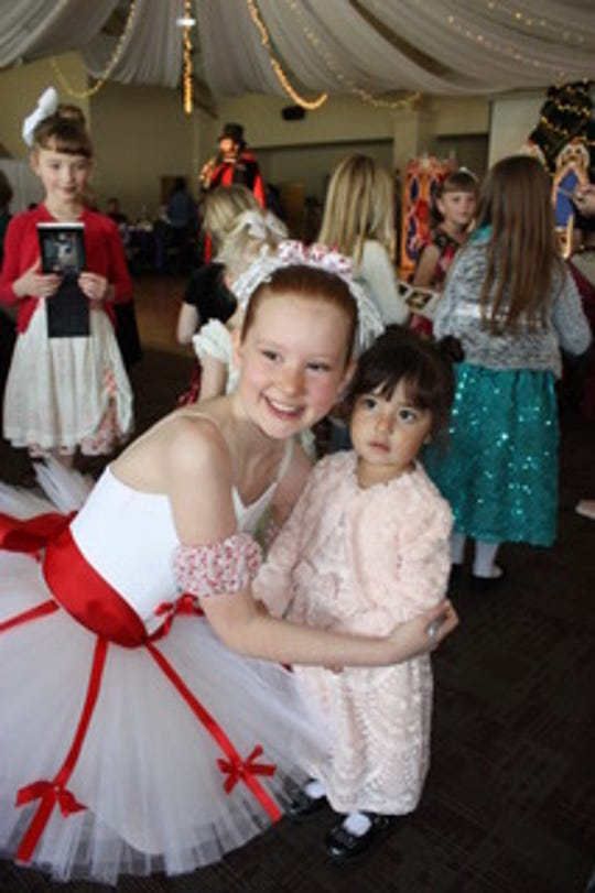 "Dali Ballet Company dancer Hannah Anderson, left, in character as ""The Nutcracker's"" Candy Cane, signs autographs at Clara's Tea Party, an annual fund-raiser and opportunity for community interaction."