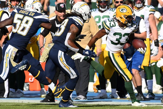 Nov 3, 2019; Carson, CA, USA; Green Bay Packers running back Aaron Jones (33) runs the ball against Los Angeles Chargers outside linebacker Thomas Davis (58) and defensive back Rayshawn Jenkins (23) during the second quarter at Dignity Health Sports Park. Mandatory Credit: Richard Mackson-USA TODAY Sports