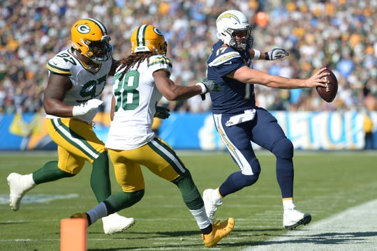 Nov 3, 2019; Carson, CA, USA; Los Angeles Chargers quarterback Philip Rivers (17) runs as Green Bay Packers nose tackle Kenny Clark (97) and cornerback Tramon Williams (38) defend during the first quarter at Dignity Health Sports Park. Mandatory Credit: Jake Roth-USA TODAY Sports
