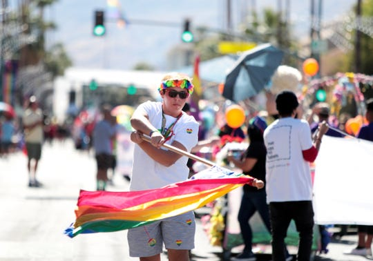 Isaiah Diaz, 16, of Los Angeles twirls a flag during the 2019 Greater Palm Springs Pride Parade in Palm Springs, Calif., on Sunday, November 3, 2019.