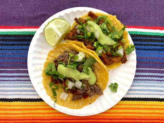 Carne asada taco (front left) and taco al pastor (rear right) with onion, cilantro, guacamole and salsa from Tacos Tijuana at the 2019 azcentral Wine & Food Experience at Salt River Fields near Scottsdale.