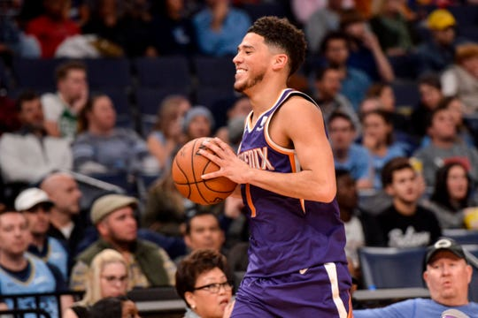 Phoenix Suns guard Devin Booker (1) laughs after stepping out of bounds in the second half of an NBA basketball game against the Memphis Grizzlies Saturday, Nov. 2, 2019, in Memphis, Tenn. (AP Photo/Brandon Dill)