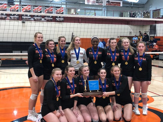 A smiling Palmyra girls volleyball team holds their district championship trophy after sweeping Garden Spot for the title last Saturday evening.