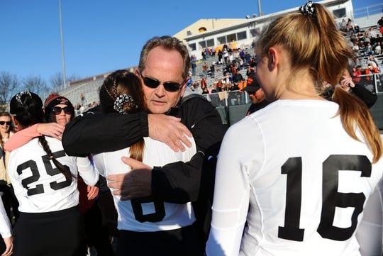 Palmyra head coach Kent Harshman hugs Anna Miller (6) after giving her her gold medal.