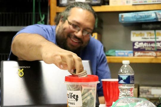 Dusty Miller, of West York, places money into a donation jar for a second-chance during his turn of Pathfinder. His group, along with 50 othersparticipated in a 25-hour long gaming marathon for the organization Extra Life, a charity that donates money to Children's Miracle Network Hospitals, Sunday, November 3, 2019. Tina Locurto photo
