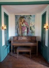 A piano is tucked into a spot that once displayed the altar of the Maytown Church. The painting of Jesus dates back to when the living room was a church.