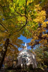 The front of the house with the steeple framed by fall foliage at its peak.
