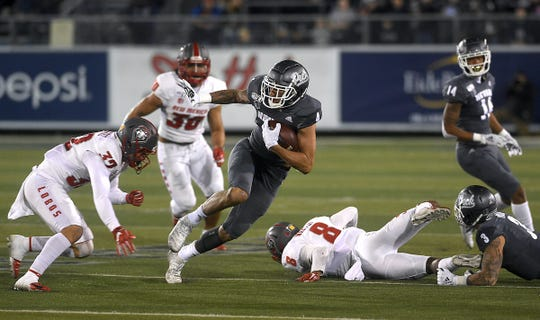Nevada's Elijah Cooks looks for extra yardage Saturday night against New Mexico.