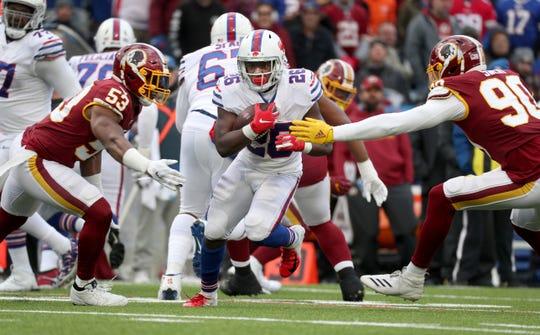 Bills running back Devin Singletary splits Redskins defenders Jon Bostic (53) and Montez Sweat.
