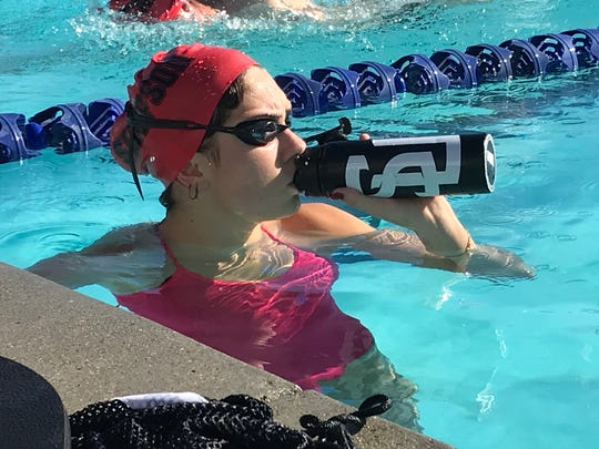 Freshman Irene Lopez hydrates during Simpson's swim practice at the Redding YMCA
