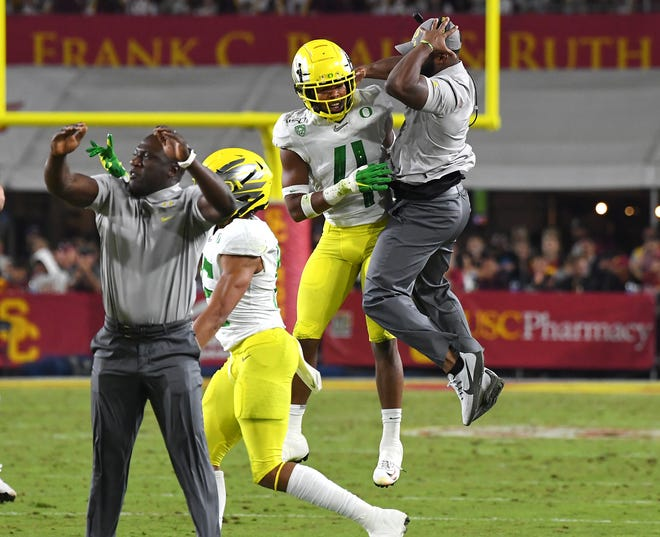 Oregon Ducks cornerback Thomas Graham Jr. (4) celebrates with coach Keith Heyward after a fumble recovery in the first half of the game against the USC Trojans at the Los Angeles Memorial Coliseum.