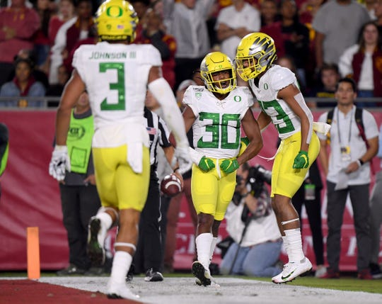 Jaylon Redd #30 of the Oregon Ducks celebrates his touchdown run with Josh Delgado #83 and Johnny Johnson III #3, to take a 14-10 lead over the USC Trojans, during the first half at Los Angeles Memorial Coliseum on November 02, 2019 in Los Angeles, California.
