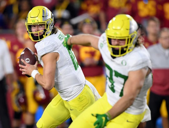 Justin Herbert #10 of the Oregon Ducks rolls out of the pocket behind Ryan Bay #87 during the first half against the USC Trojans at Los Angeles Memorial Coliseum on November 02, 2019 in Los Angeles, California.