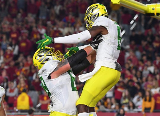 Oregon Ducks wide receiver Juwan Johnson (6) celebrates with Ducks offensive lineman Shane Lemieux (68) after scoring a touchdown in the second half against the USC Trojans at the Los Angeles Memorial Coliseum.