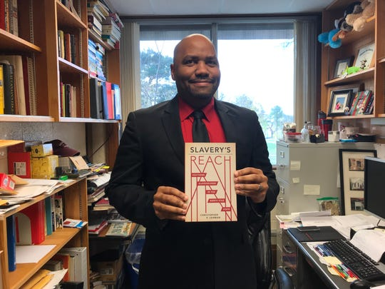 """Christopher Lehman, a St. Cloud State University professor, poses for a photo with his book """"Slavery's Reach: Southern Slaveholders and the North Star State"""" in his office Wednesday, Oct. 23, 2019."""