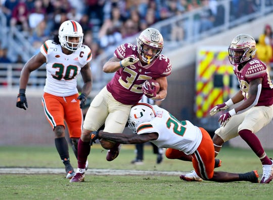 Nov 2, 2019; Tallahassee, FL, USA; Miami Hurricanes safety Gurvan Hall Jr (26) tackles Florida State Seminoles tight end Gabe Nabers (32) during the second half at Doak Campbell Stadium. Mandatory Credit: Melina Myers-USA TODAY Sports