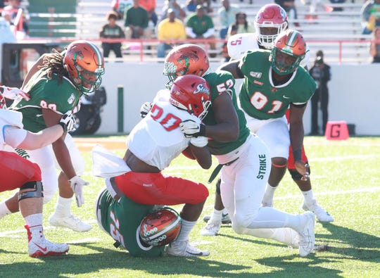 FAMU linebacker Derrick Mayweather leads a gang tackle against Delaware State running back Bryant Dallas on Saturday, Nov. 2, 2019 at Bragg Memorial Stadium.