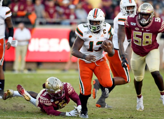 Nov 2, 2019; Tallahassee, FL, USA; Miami Hurricanes running back DeeJay Dallas (13) runs the ball past Florida State Seminoles linebacker Dontavious Jackson (5) during the second half at Doak Campbell Stadium. Mandatory Credit: Melina Myers-USA TODAY Sports