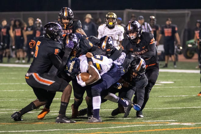 The Ventura College defense works together to tackle Canyons running back Cayden Dunn on Saturday night at the VC Sportsplex. VC lost to COC, 48-38.
