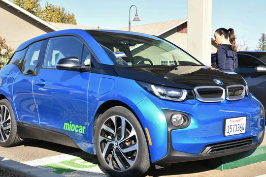 Abigail Solis enters Miocar at Highland Gardens in Visalia on Nov. 1, 2019. The electric car-share is available to all residents through a new Valley Air District initiative.