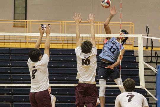 Suffern's Jo'el Emanuel (13) is ready to spike the ball, as Scarsdale's Dorji Phuntsho (8) and David Lang (16) attempt to block it.