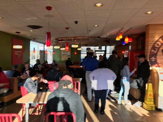 Some Newark Popeyes patrons eat while others wait to place orders and get sandwiches.