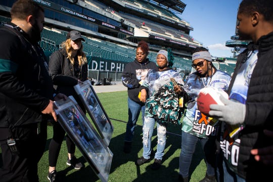 The family of Troy Haynes are presented with framed photos of Troy's last visit to see the Eagles play before his passing shot by The News Journal Sunday at Lincoln Financial Field. Haynes lost his battle with kidney cancer Sept. 29, 2019. The Philadelphia Eagles staff and kicker Jake Elliot surprised the family with the photos and a football after inviting them to watch the Eagles take on the Chicago Bears Sunday.