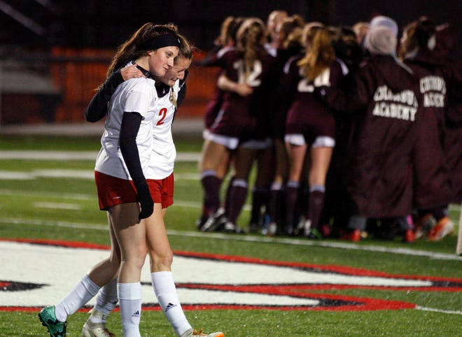 Rosecrans' Ella Lambert, left, consoles teammate Kailey Zemba as they walk off the field after a 2-0 loss to Columbus Academy in a Division III regional finals match on Saturday, at Coshocton's Stewart Field