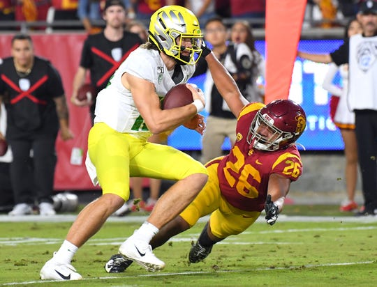 Oregon quarterback Justin Herbert runs with the ball past Southern California linebacker Kana'i Mauga to score a touchdown during the first half at the Los Angeles Memorial Coliseum.