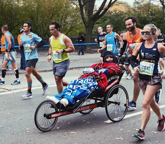 Joe Rooney (right, orange shirt) pushes Mikey Nichols in the New York City Marathon