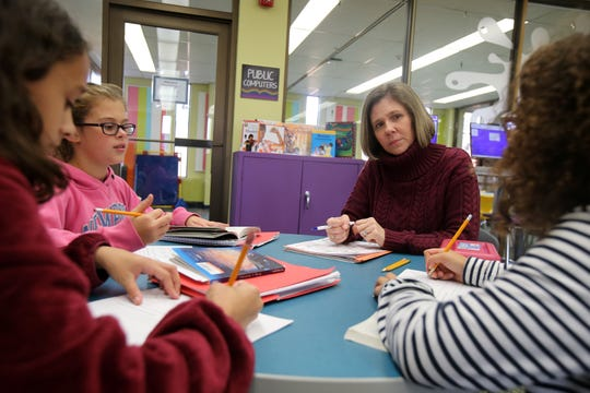 (center) Christin Agee, owner of Shore I Can, a five-year-old Neptune-based provider of children's tutoring services in math and reading, holds a writing clinic for (L-R) Kherri Kinkela, 9, Keira Schuetz, 11, and Alianna Agee, 10, all of Neptune,  at the Neptune Library in Neptune, NJ Monday, November 4, 2019.