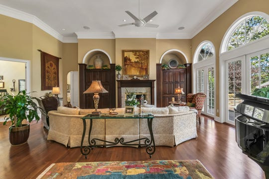 The living room features a set of french doors and custom wall designs.