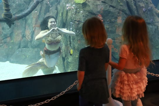 Mermaid Amira expresses affection for some young aquarium visitors.