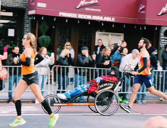 Joe Rooney (far right) pushes Mikey Nichols in the New York City Marathon.