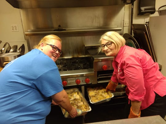 Hope Ross, left, and Alicia Beck check on chickens roasting for a dinner at Johnson City Elks Lodge 2821. Ross is a trustee of the lodge, while Beck has volunteered as the lodge's chaplain and a member for 15 years.