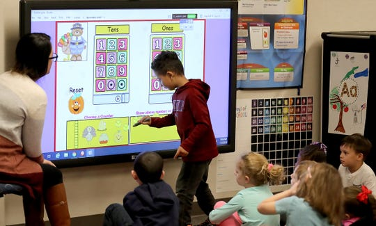 """Kindergarten student Julius Allen uses the smart screen to answer a question posed by teacher Hae Eun Su during class at Silverdale Elementary School on Monday. Central Kitsap School District is offering """"jump start"""" kindergarten classes at Silverdale, Silver Ridge and PineCrest elementary schools starting in February."""