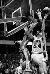 Sixers Bobby Jones (24) flips a short hook shot over the up stretched arms of Atlanta Hawks John Brown.