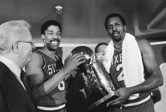 Julius Erving, left, and Moses Malone, right, hold the NBA Championship trophy after defeating the Los Angeles Lakers in  Los Angeles.