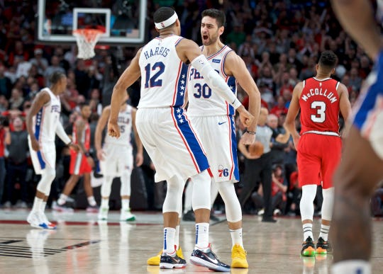 Furkan Korkmaz, right, and Tobias Harris react after Korkmaz made a game winning basket against the Portland Trail Blazers Saturday to win 129-128.