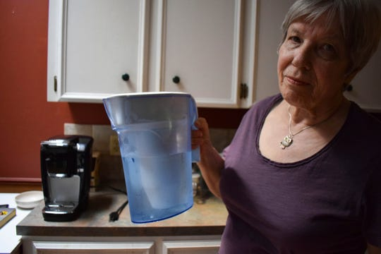 Monica Baehr holds a Zero Water filter for drinking water at her home in Calgary, Alberta, Canada on Aug. 6, 2019. Hundreds of thousands of Canadians from coast to coast have been unwittingly exposed to levels of lead in their drinking water, with contamination in several cities consistently higher than they ever were in Flint, Michigan, according to an investigation that tested drinking water in hundreds of homes and reviewed thousands more previously undisclosed results. ( via AP)