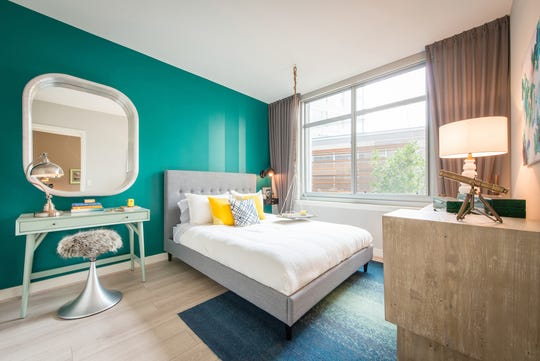 Luxury property managers who are upgrading apartments may create an accent wall with a bold paint color or wallpaper. Pillows with a pop of color and a warm rug placed over a plank floor give personality to an apartment bedroom at Dock 79 in Washington, D.C.