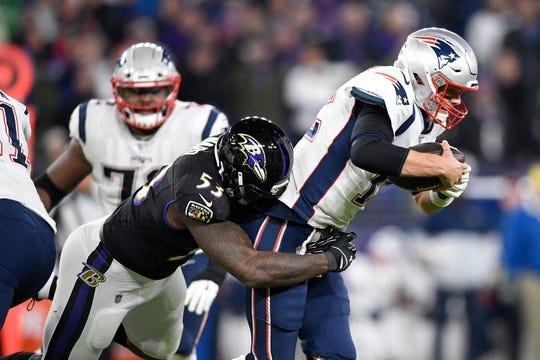 Ravens defensive end Jihad Ward (53) sacks Patriots quarterback Tom Brady (12) on a third down play in the second half on Sunday.